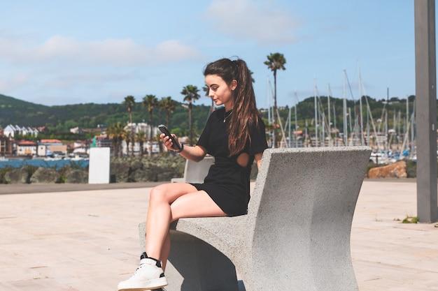 Jonge vrouw op een bankje met een mobiele telefoon in hendaia, baskenland.