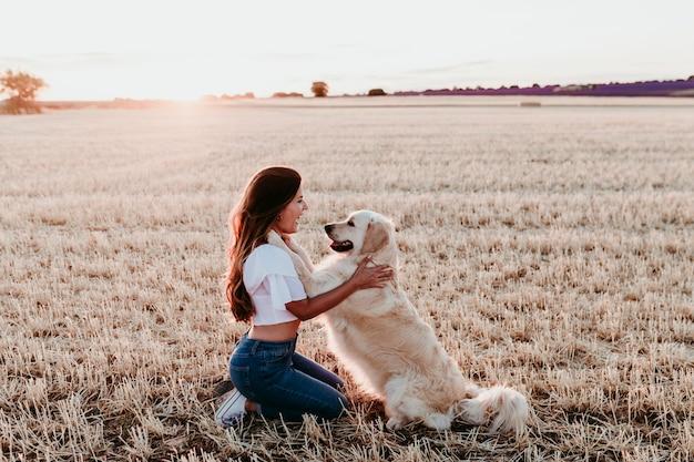 Jonge vrouw op een geel gebied met haar golden retrieverhond bij zonsondergang. huisdieren buiten