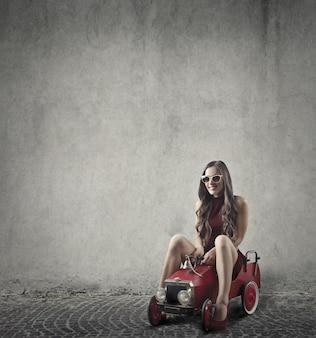 Jonge vrouw op een kleine speelgoedauto
