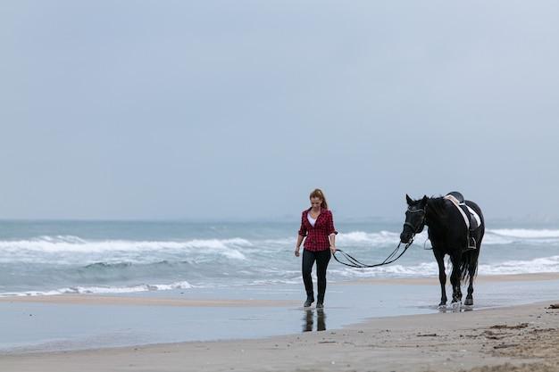 Jonge vrouw op een paard op het strand op een bewolkte dag