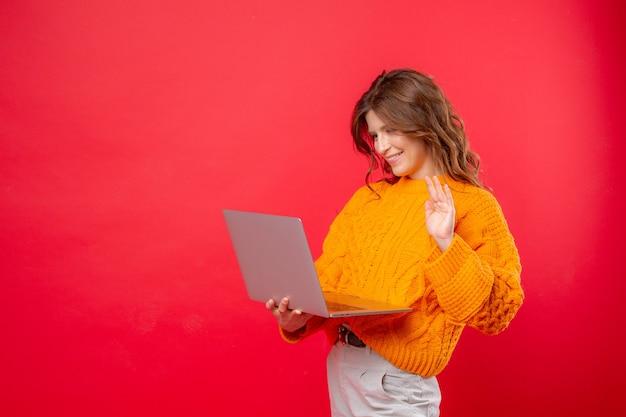 Jonge vrouw op een rode communiceert met een laptop via het netwerk