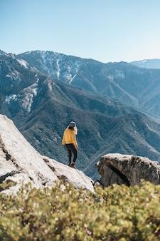 Jonge vrouw op een rots in de bergen