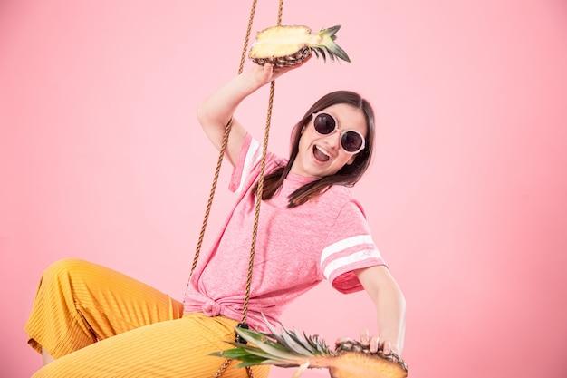 Jonge vrouw op een schommel op een roze