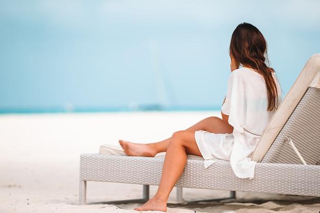 Jonge vrouw op een tropisch strand met hoed