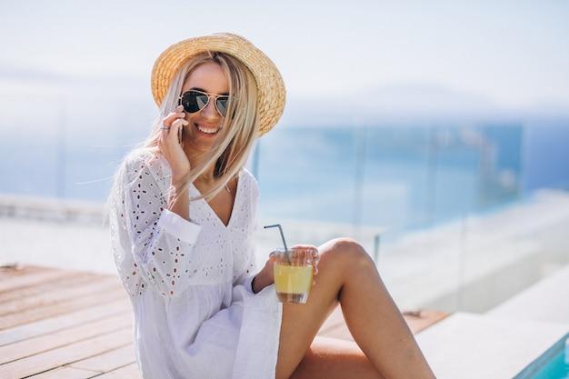Jonge vrouw op een vakantie bij het zwembad met behulp van de telefoon