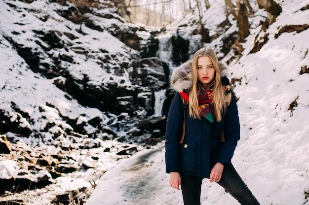 Jonge vrouw op een wandeling in een winter bos