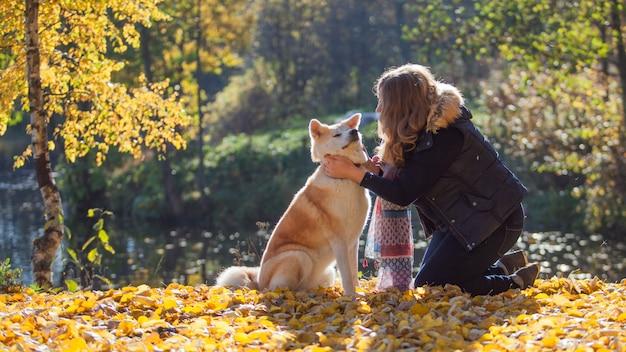 Jonge vrouw op een wandeling met haar hondenras akita inu