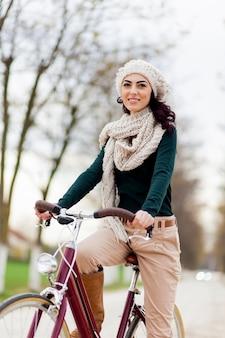 Jonge vrouw op fiets in de winter