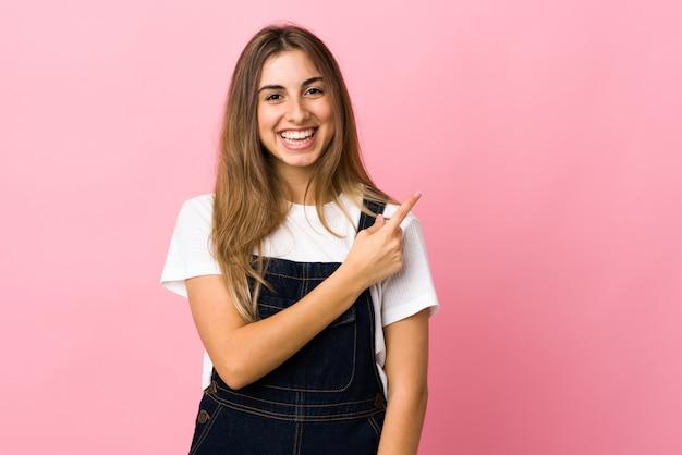 Jonge vrouw op geïsoleerd roze wijzend naar de zijkant om een product te presenteren