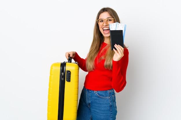 Jonge vrouw op geïsoleerd wit in vakantie met koffer en paspoort