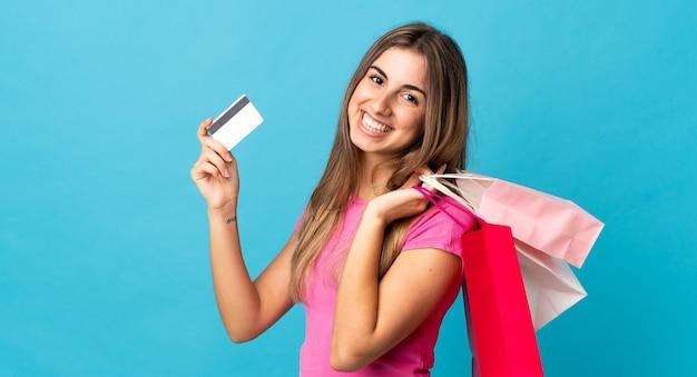 Jonge vrouw op geïsoleerde blauwe bedrijf boodschappentassen en een creditcard