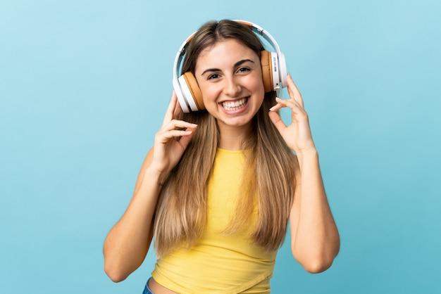 Jonge vrouw op geïsoleerde blauwe het luisteren muziek