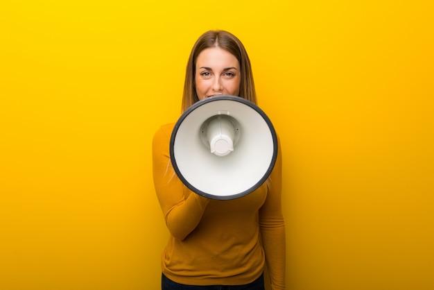 Jonge vrouw op gele achtergrond die door een megafoon schreeuwt om iets aan te kondigen