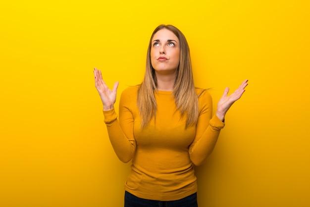 Jonge vrouw op gele achtergrond die door een slechte situatie wordt gefrustreerd