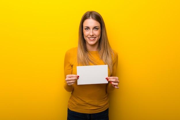 Jonge vrouw op gele achtergrond die een aanplakbiljet voor tussenvoegsel een concept houdt