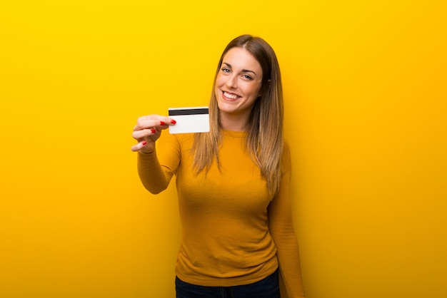 Jonge vrouw op gele achtergrond die een creditcard houdt