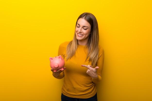 Jonge vrouw op gele achtergrond die een piggybank houdt