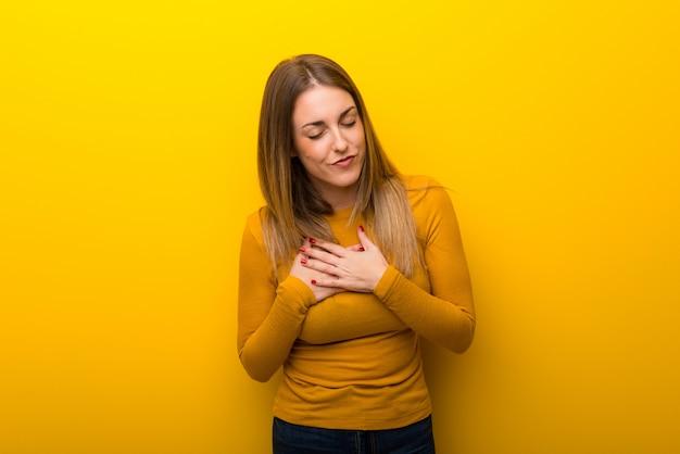 Jonge vrouw op gele achtergrond die een pijn in het hart heeft
