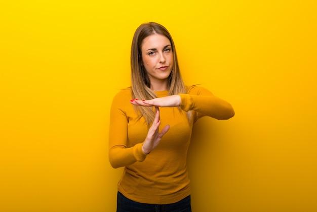 Jonge vrouw op gele achtergrond die eindegebaar met haar hand maken om een handeling tegen te houden