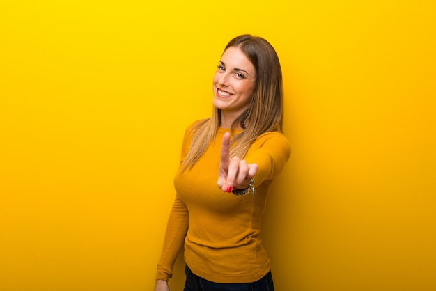 Jonge vrouw op gele achtergrond die en een vinger toont opheft