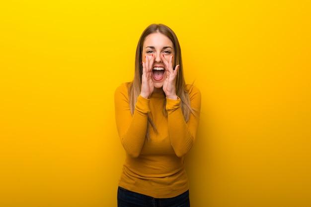 Jonge vrouw op gele achtergrond die en iets schreeuwt aankondigt