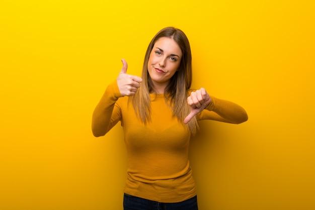 Jonge vrouw op gele achtergrond die goed-slecht teken maakt. onbeslist tussen ja of nee
