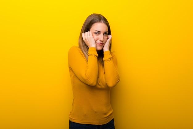Jonge vrouw op gele achtergrond die oren behandelt met handen. gefrustreerde uitdrukking