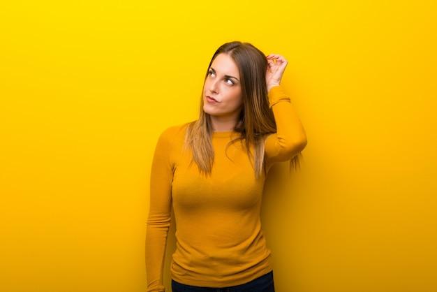Jonge vrouw op gele achtergrond die twijfels hebben terwijl het krassen van hoofd