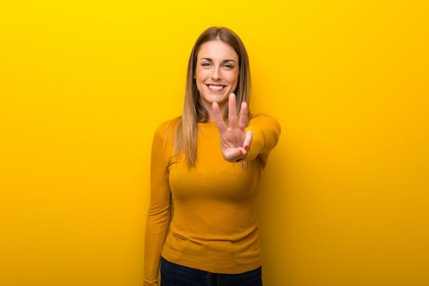 Jonge vrouw op gele achtergrond gelukkig en drie met vingers tellen