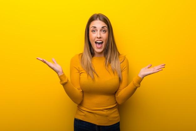 Jonge vrouw op gele achtergrond met verrassing en geschokte gelaatsuitdrukking