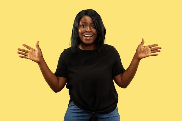Jonge vrouw op gele studio