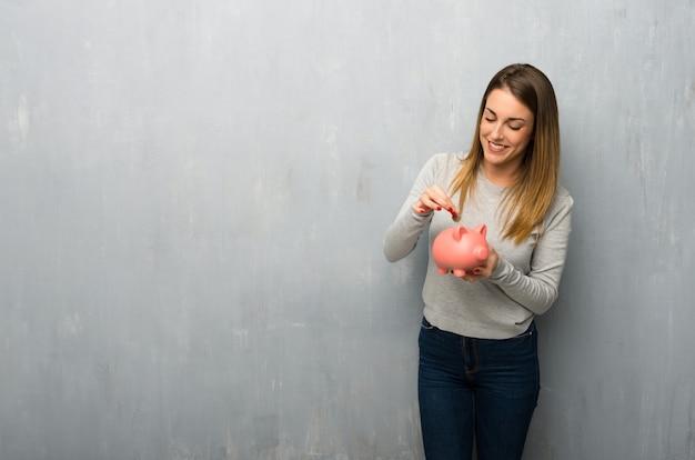 Jonge vrouw op geweven muur die een spaarvarken neemt en gelukkig omdat het volledig is
