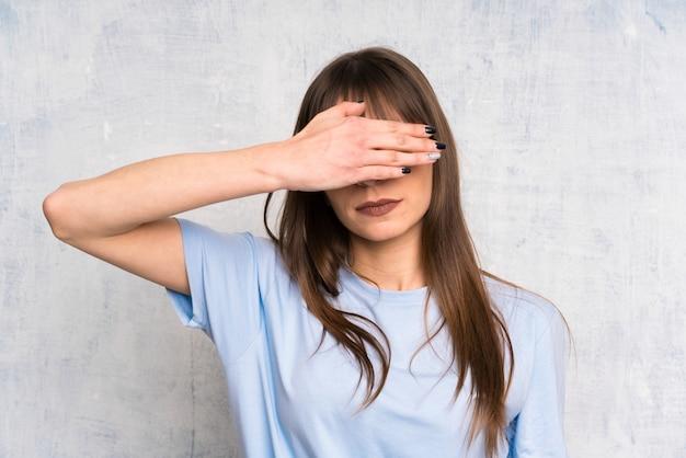Jonge vrouw op grungeachtergrond die ogen behandelen door handen