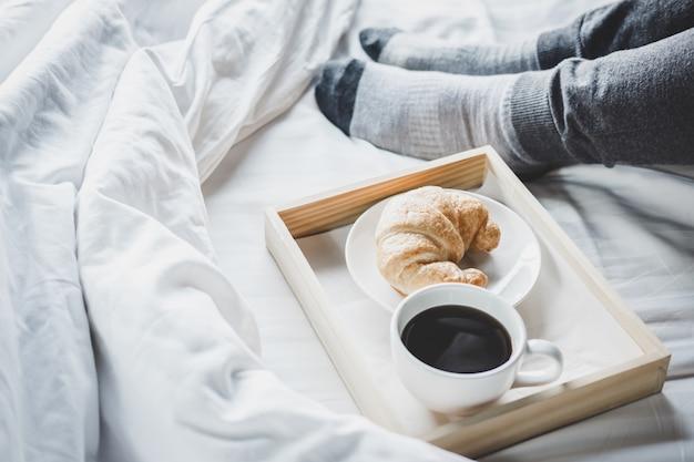 Jonge vrouw op het bed met het genieten van lezingskrant in vakantie en ochtendkoffie