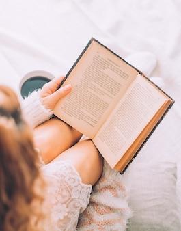 Jonge vrouw op het bed met oud boek en kopje koffie geniet van haar verblijf.