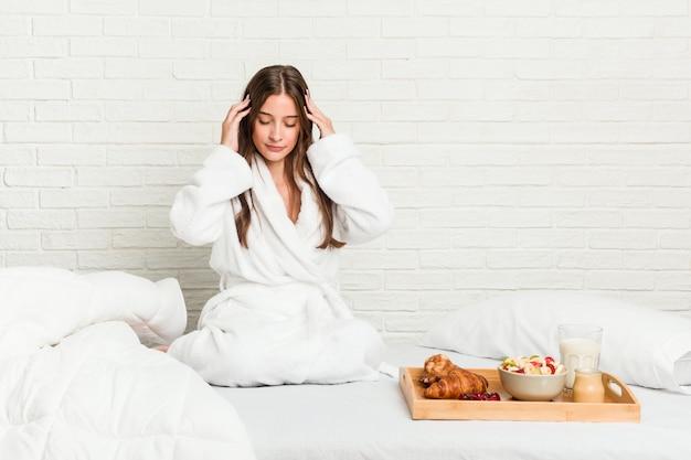 Jonge vrouw op het bed wat betreft tempels en het hebben van hoofdpijn