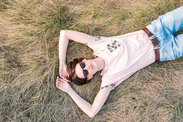Jonge vrouw op het gras dat tijd vergt om de lente te waarderen