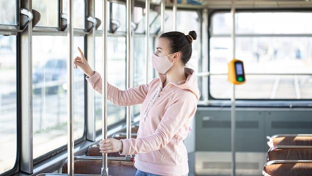 Jonge vrouw op het openbaar vervoer tijdens de pandemie.