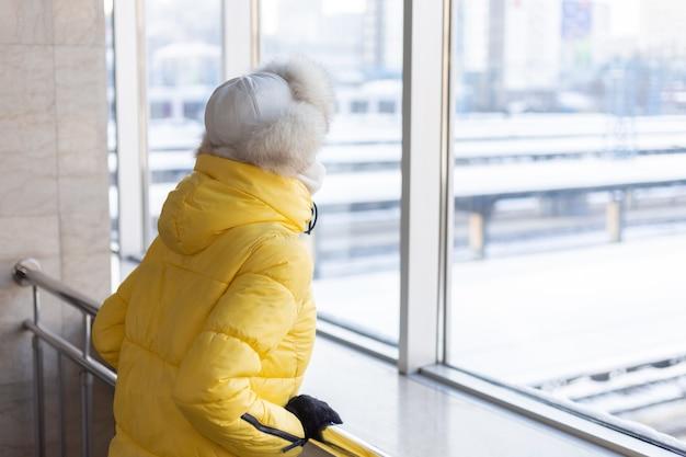 Jonge vrouw op het station in een beschermend masker op het gezicht in winterkleren passagier