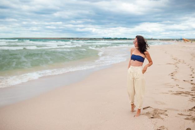 Jonge vrouw op het strand in bewolkte dag