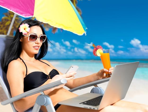 Jonge vrouw op het strand met laptop en mobiele telefoon die sms verzendt.