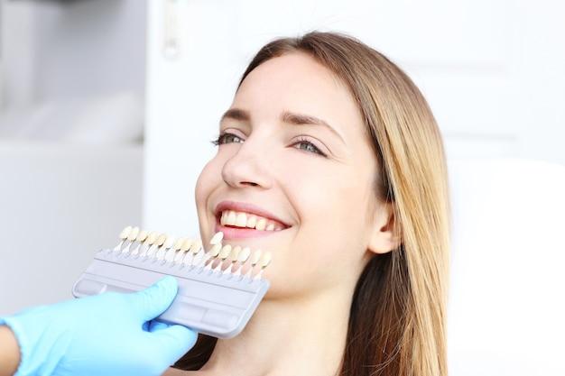 Jonge vrouw op het tandartskantoor die de kleur van de tanden controleert en selecteert and