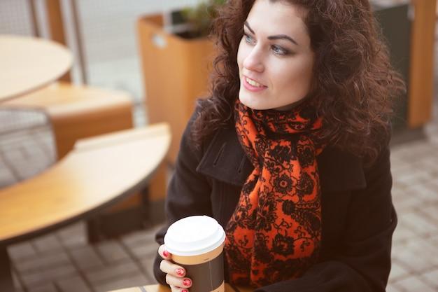 Jonge vrouw op het terras van een café met een mok warme koffie in haar hand
