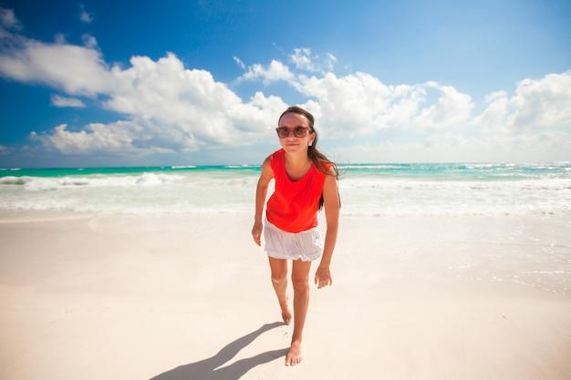Jonge vrouw op het witte exotische strand dat camera bekijkt
