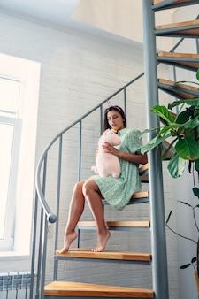 Jonge vrouw op houten trappen in modern huis.