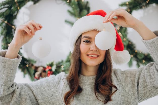Jonge vrouw op kerstmis met kerstmisspeelgoed