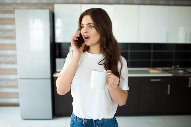 Jonge vrouw op keuken. emotioneel praten over de telefoon en me afvragen. houd witte beker met drankje in de hand.