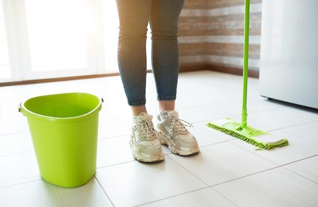 Jonge vrouw op keuken. stand alone op schone vloer na wassen met dweil en water. emmer aan de zijkant. daglicht.