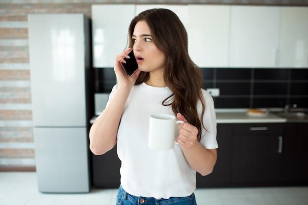 Jonge vrouw op keuken. vrouwelijk model praten over de telefoon met wonder en kijk naar links. witte beker in de hand houden. daglicht in de keuken.