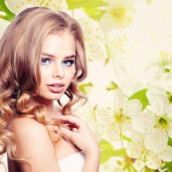 Jonge vrouw op lente bloemen achtergrond